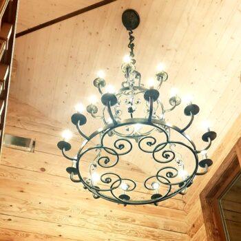 Подвесная кованая люстра в деревянном доме